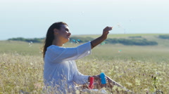 Beautiful young woman lets bubbles float on the breeze, in slow motion Stock Footage