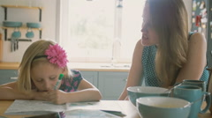 Mother is smiling while talking to her little daughter who is colouring a Stock Footage