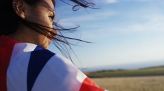 Attractive woman wears a union jack flag as she looks towards horizon Stock Footage