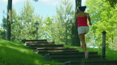 Running girl on stairway in slow motion. African woman running up on stairs Stock Footage