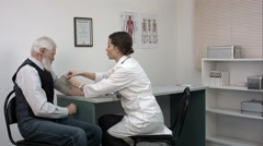 Doctor checking old man patient arterial blood pressure. Health care Arkistovideo