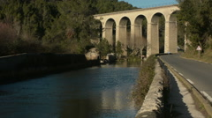 Road traffic and the arched pont-aqueduct of Galas, France Stock Footage