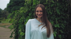 Attractive girl standing near the green tree and smiles, straightens hair Stock Footage