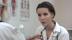 Woman doctor listening to senior patient talking Stock Footage