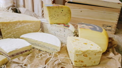 A variety of cheeses. Lying on sackcloth and decorative hay Stock Footage