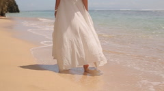Young woman in white dress walking alone on the beach Stock Footage