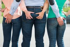 Rear View Of Friends Holding Each Other's Buttock Stock Photos