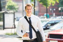 Portrait Of Happy Young Businessman With Disposal Cup Stock Photos