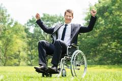 Happy Young Disabled Man On Wheelchair With Raised Arms In Park - stock photo