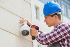 Young Male Technician Installing Camera On Wall Using Electric Cordless Drill Stock Photos
