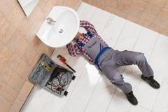 High Angle View Of Male Plumber Lying On Floor Repairing Sink In Bathroom Stock Photos