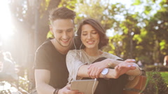 Young beautiful couple smiling, speaking, looking at tablet, sitting in city Stock Footage