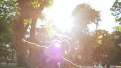 Young beautiful couple rejoicing, smiling, walking in park. Slow motion Stock Footage