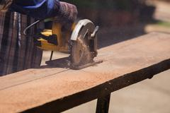 Carpenter use electric saw to sawing wood Stock Photos