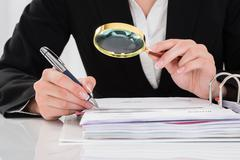Close-up Of Auditor Inspecting Financial Documents At Desk Stock Photos