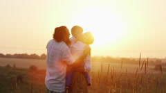 Big family hugging at sunset. Parents and two children Stock Footage