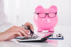 Person Calculating Bill With Pink Piggybank On Desk - stock photo