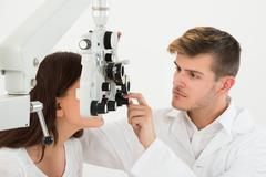 A Male Ophthalmologist Adjusting The Panel Of Phoropter While Examining Femal - stock photo