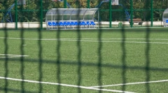 Empty football field footage shot through a wire fence Stock Footage