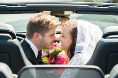 Newlyweds Young Smiling Couple Kissing In The Wedding Car - stock photo