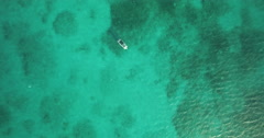 Aerial down to boat in clear waters in Belize Stock Footage