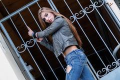 Young beautiful teenager girl standing on background of openwork lattice, roc Stock Photos