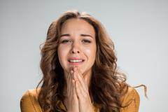 Woman is looking imploring over gray background Stock Photos