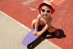 Small child in shorts and sunglasses sitting on a skateboard in the summer Stock Photos
