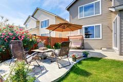 Beautiful landscape design for backyard garden and patio area on concrete flo Stock Photos