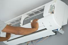 Worker installing air conditioning Stock Photos