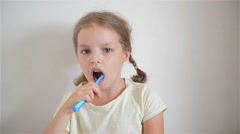 A little girl brushing her teeth with a brightly colored toothbrush Stock Footage