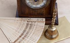 Still life, brass bell, antique clock and carved wooden fan Kuvituskuvat