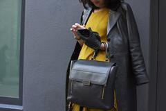 Stylish woman leans on wall using smartphone, crop, close up Stock Photos