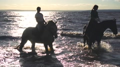 Two women ride on horse at river beach in water sunset light Stock Footage