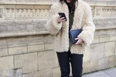 Woman wearing sheepskin jacket using smartphone, crop Stock Photos