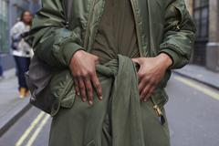 Man wearing military style olive green clothes, mid section Stock Photos