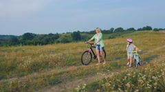 Steadicam shot: Mother and daughter walking with bicycles Stock Footage