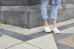 Low section of woman in jeans and white shoes in the street Stock Photos