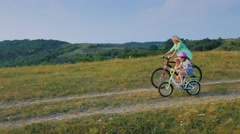 Steadicam shot: Mother and daughter 5 years ride bicycles through the Stock Footage