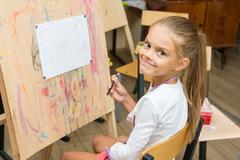 Girl happily looks into the frame on a drawing lesson Stock Photos