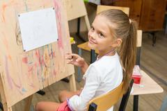 Girl happily looks at the teacher at a drawing lesson Stock Photos