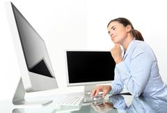 Woman in office at desk in front of computer screen, mouse click Kuvituskuvat