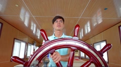 Young captain drives a tourists boat in Ha Long Bay Stock Footage
