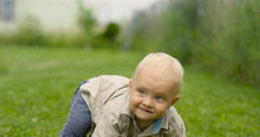 The one year old cute fair-head boy is making his first steps on green grass in Stock Footage