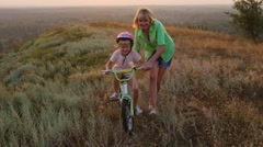The first children's dreams - Mom teaches daughter to ride a bike Stock Footage