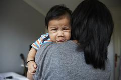 Mother Comforting Unhappy Baby Boy Over Shoulder Stock Photos