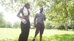 Young woman with personal trainer walking through the park & looking at tablet Stock Footage