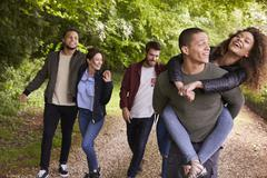 Happy friends walking and piggybacking in a country lane Stock Photos