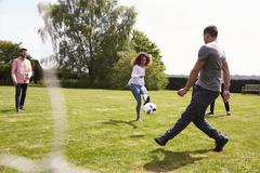 Adult friends having fun with a football on a playing field Stock Photos