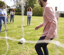 Friends have fun playing with a football on a playing field Stock Photos